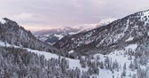 dolomites : Side aerial to snowy valley with woods forest at Sella pass.Sunset or sunrise,cloudy sky.Winter Dolomites Italian Alps mountains outdoor nature establisher.4k drone flight Stock Footage