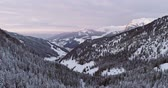 sella : Backward aerial to snowy valley with woods forest at Sella pass.Sunset or sunrise,cloudy sky.Winter Dolomites Italian Alps mountains outdoor nature establisher.4k drone flight Stock Footage