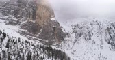 dolomites : Backward aerial with snowy mountain and woods forest at Sella pass.Cloudy bad overcast foggy weather.Winter Dolomites Italian Alps mountains outdoor nature establisher.4k drone flight