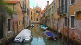 Perspective of small side canal with church in the end and moored boats in Venice, Italy