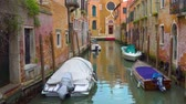 венето : Perspective of the small side canal with moored boats in Venice, Italy Стоковые видеозаписи