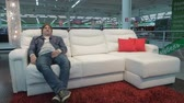 четыре человека : MOSCOW, RUSSIA - SEPTEMBER 13, 2017: Happy man testing automatically folding sofa in a market. Man choosing new smart sofa-transformer in furniture store Стоковые видеозаписи