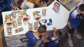 atributo : MOSCOW, RUSSIA - AUGUST 5, 2018: Tourists buy official souvenirs - in the point of sale of sports store in GUM, Moscow. Father buys for his son the cap with Zabivaka toy. Video was taken from above