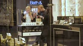disinterest : Moscow, Russia - September 16, 2018: Woman sniffing smell perfume with her hasbent in the beauty store. A girl with her boyfriend chooses the scent of perfumes in boutique. The husband while looking into the smartphone. Couple buys perfume in aroma boutiq