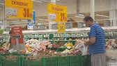 average age : MOSCOW SEPTEMBER 29, 2018: People buy products in Auchan. Man and woman pick up vegetables in plastic bags from the counter in Ashan hypermarket. Flat video Stock Footage