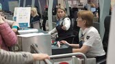 обычай : Moscow, Russia - May 6, 2019: Two female airport security personnel checking identification at a check-in or boarding counter at the departure terminal holding the passports of two male passengers. Passengers check-in. Employee checks passport information Стоковые видеозаписи