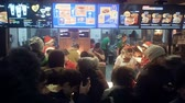 wachtrij : Moscow, Russia -January 1, 2019: Crowded McDonalds on New Years Eve. Many visitors crowded around the order table of Mcdonalds, huge crowd standing in queue in fast food restaurant. McDonalds employees dressed in Santaclaus red caps perform different task