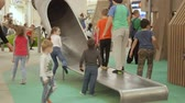 plazit se : Moscow, Russia - November 11, 2019: Children of different ages frolic down a hill in the shape of a tunnel or a big pipe. Kids plaing in the play area of the shopping center under parental control. Playful Children frolic in the gaming zone of the shoppin