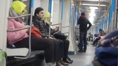 pendulares : MOSCOW, RUSSIA - NOVEMBER 21, 2019: Movement of metro train carriag. People in warm clothes sitting in underground carriage an using smartphones. A man sitting thinking about something, Girl and woman surfing wi-fi in smartphone. Train with through passag