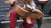 violino : Moscow, Russia - June 13, 2019: Street musician dressed in vintage ethnic oriental clothes play music on traditional Middle Eastern musical instrument hurdy-gurdy also named wheel fiddle, wheel vielle. Contains sound