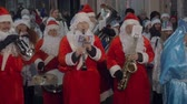 sax : MOSCOW - JAN, 01, 2018: SSantaclaus Street Procession. A lot of people dressed as Santa Claus and Snow Maiden walk along the streets of Moscow on New Years Day. Congratulate on the holiday and play the saxophone. Stock Footage
