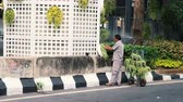 buda : Bangkok, Thailand - May 8, 2019: Greening of Bangkok city. A gardener decorates the streets of the city with greenery. Male worker plants live plants near a big city in a big city.