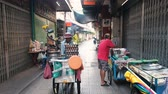 indigeni : Bangkok, Thailand - May 18, 2019: Street Food Vendor Walking The Road With Vending Cart on a Market in Thailand. Other people are preparing snack for sale in the market