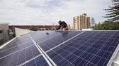 Solar technician installing solar panels on roof.
