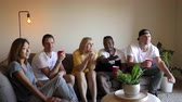Group of young multinational adults watching TV. Slider shot