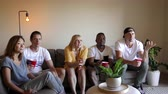 livingroom : Group of young multinational adults watching TV. Slider shot