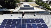 photovoltaic : Aerial shot of solar panel technician with drill installing solar panels on roof on a sunny day