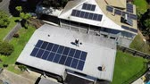 Aerial shot of solar panel technician with drill installing solar panels on roof on a sunny day