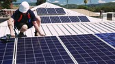 renewable : Solar panel technician with drill installing solar panels on roof on a sunny day