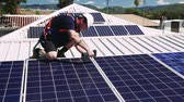technician : Solar panel technician with drill installing solar panels on roof on a sunny day