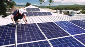 技术 : Solar panel technician with drill installing solar panels on roof on a sunny day