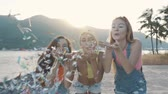 confete : Three friends women blowing a spray of confetti on the beach at sunset. Stock Footage