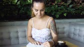 journalist : Young prety woman with tattoo writing in her journal, diary.