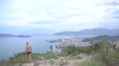 clap : Fit funny man runner happy and celebrating success. Male jump and stand on top of the mountain, cheering in winning gesture and clap hands. Beautiful city view