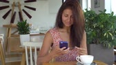 Woman banking online using smartphone and credit card in cafe