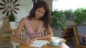 Woman writes in notepad in cafe. Stock mozgókép