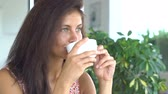 Beautiful young girl drinking coffee and smiling. Stock mozgókép