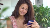 Beautiful emotional young woman texting on mobile phone.