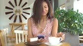 Girl listen to music on smartphone with headphones and drink coffee.