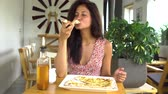 Woman eating cheese pizza slice Stock mozgókép