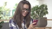 Woman using app on smartphone drinking coffee smiling, texting on mobile phone Stock mozgókép