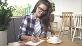 Stylish young girl writes in the journal in cafe Stock mozgókép