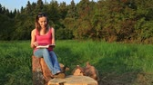 casual : Young woman sitting in a park and reading a book, HD Stock Footage