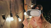 head mounted display : Young woman using Virtual Reality Glasses. Virtual reality mask. VR. Retro loft Christmas background with light bulbs. Close up shot Stock Footage