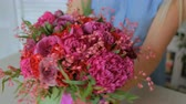 goździk : Professional woman floral artist, florist showing beautiful wedding bouquet at workshop, flower shop. Close up shot. Floristry, handmade and small business concept Wideo