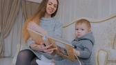 меланхолия : Young mother and her baby son looking photobook togerher at home. Family, childhood and leisure concept