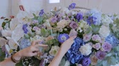 compor : Professional woman floral artist, florist making large floral basket with flowers at workshop, flower shop. Floristry, handmade and small business concept