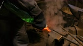 クエンチ : Professional blacksmith working with metal at forge, workshop. Handmade, craftsmanship and blacksmithing concept
