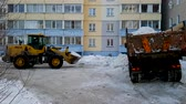 hógolyó : Snow in the yard of a housing estate. Snow loading in the dump truck for export. Winter time.