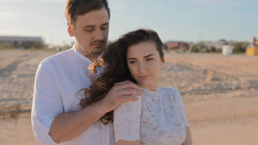 романтика : Caucasian young man and woman in white clothes cuddle on the beach. He pats her on the shoulder, she like that.