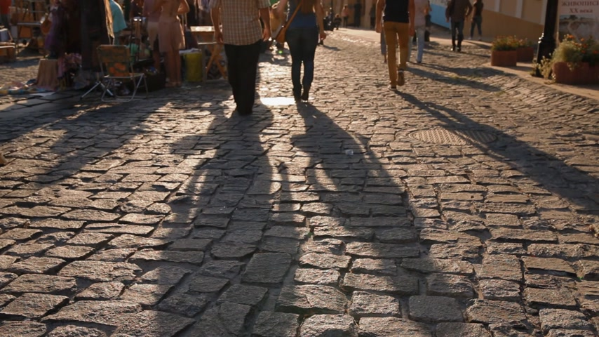 macadam : Long shadow of walking in sunset light people on macadam..Group of people walk down the street. No face. Stock Footage