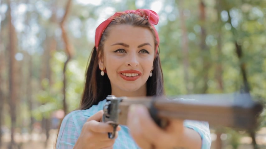 pinup : Caucasian woman pose to photographer holding a gun and sighting.She stand in the pine wood and smile to the camera.