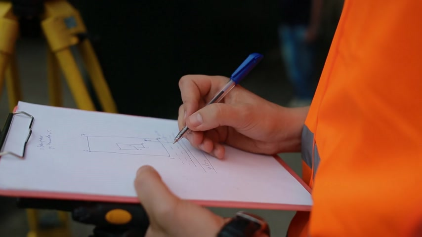 levelling : Surveyor makes plan of the land on the paper. Closeup shot. Stock Footage