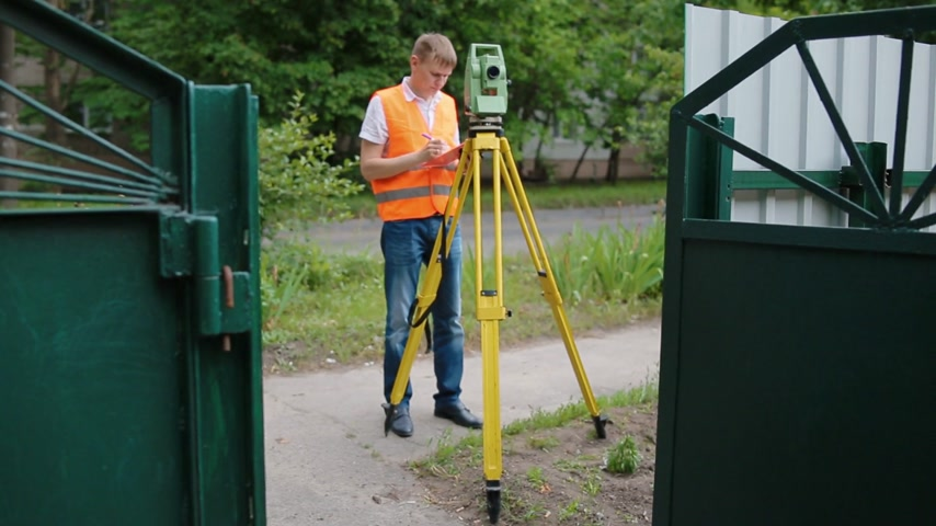 levelling : Surveyor at work measuring the distance. One caucasian man in orange vest. Overall plan.Warm season.