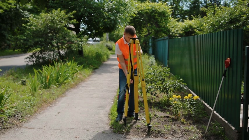 levelling : Worker in orange vest fold geodetic device for surveying