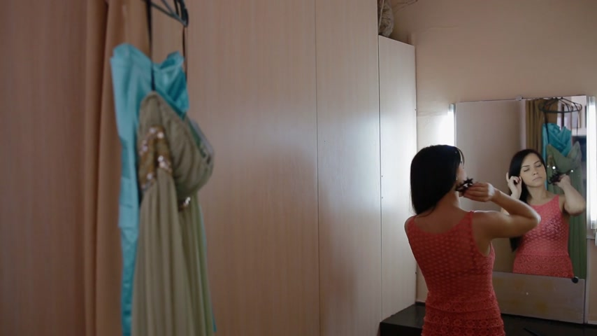 dressing room : Young woman primp in the dressing room before photo shoot. She try on a dress and look to the mirror. Stock Footage
